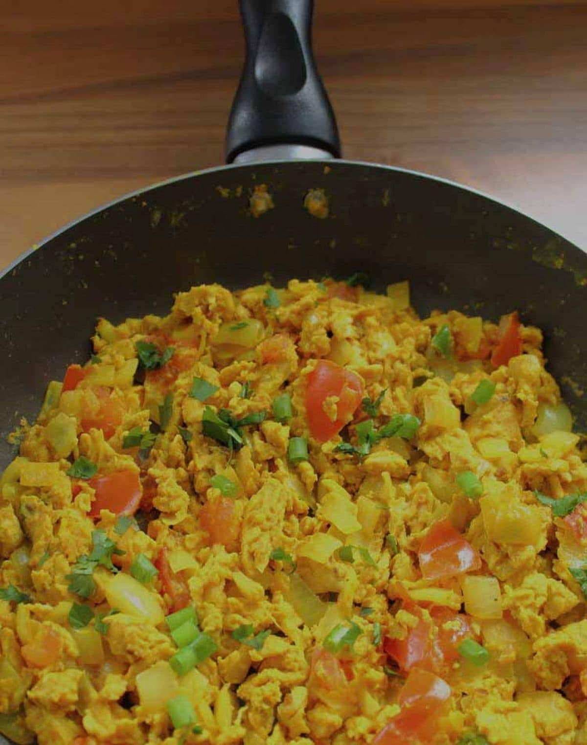 Birds eye view of half a pan of Indian scrambled eggs garnished with coriander.