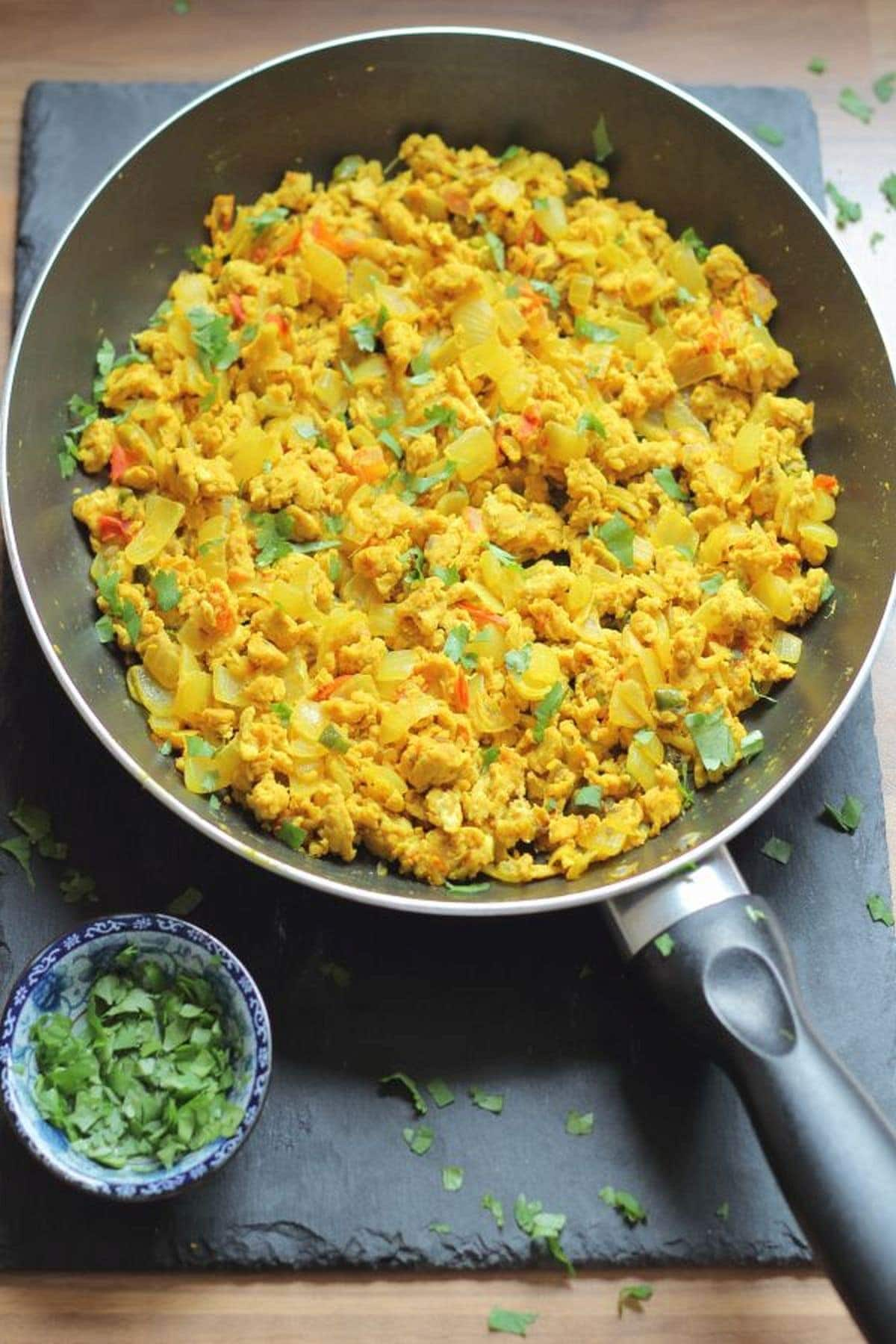 Birds eye view of a large pan of Indian scrambled eggs on a black slate with a dish of chopped coriander to the bottom left.