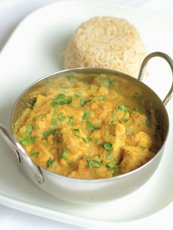 A balti dish of lighter chicken korma on a serving plate with a portion of wholegrain rice in the background.