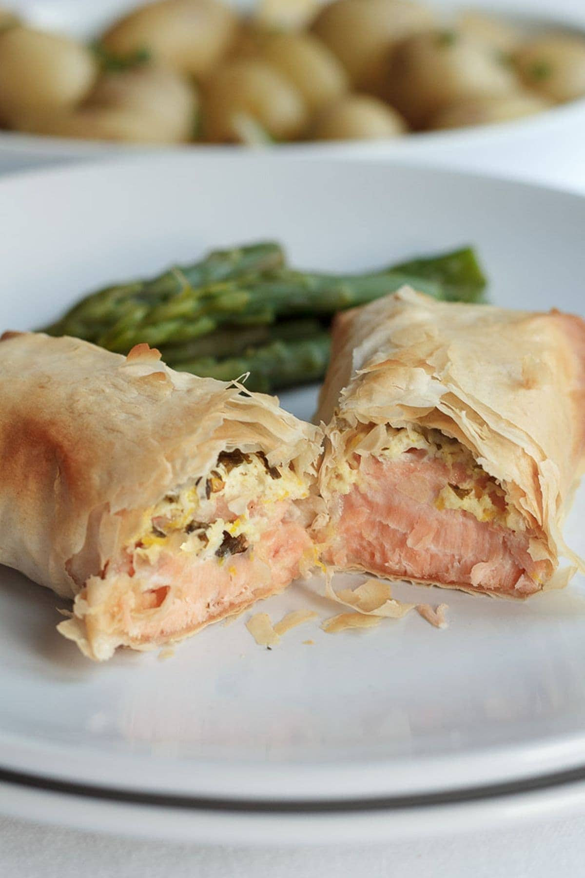 A salmon filo parcel cut in half on a plate with asparagus in the background.
