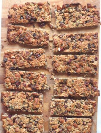 12 fruit and nut snack bars cut up on a chopping board.