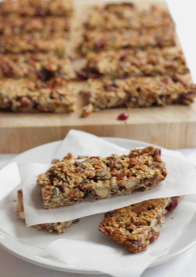 Three fruit and nut snack bars on a plate separated by greaseproof paper. The rest of the bars are cup up on a chopping board in the background.