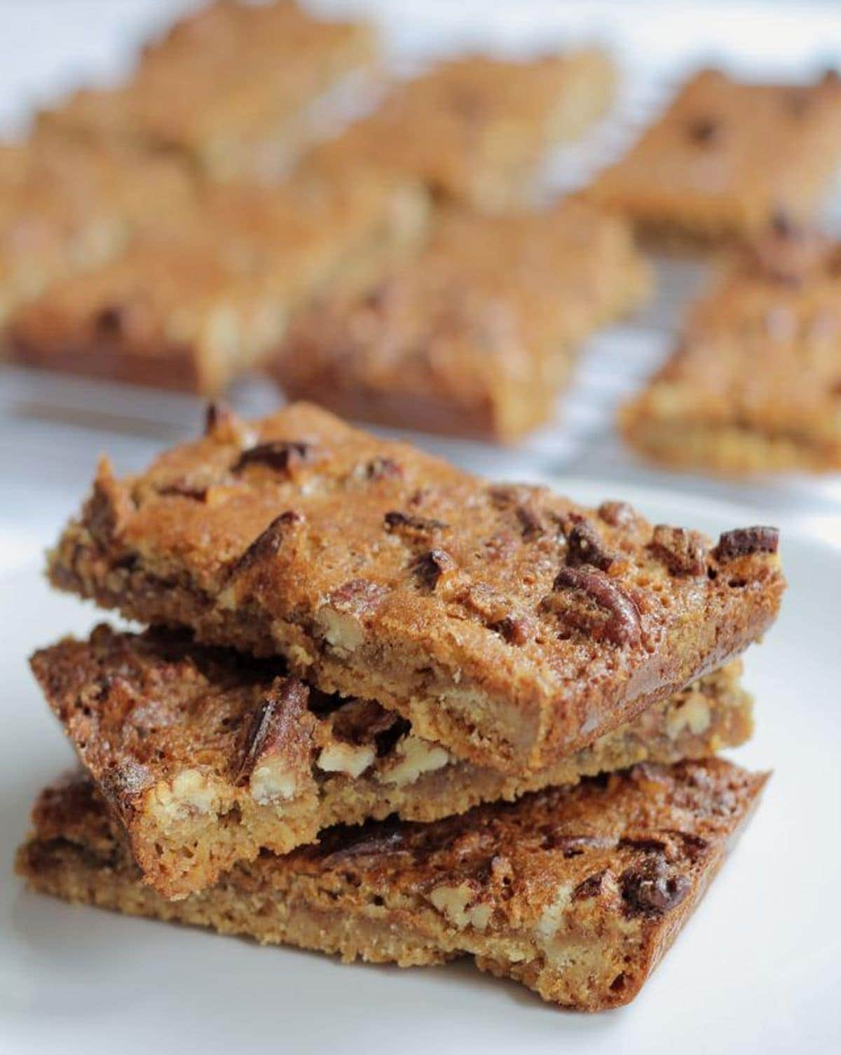 Three pecan nut biscuit bars one on top of the other with the rest of the bars on a wire baking rack behind.