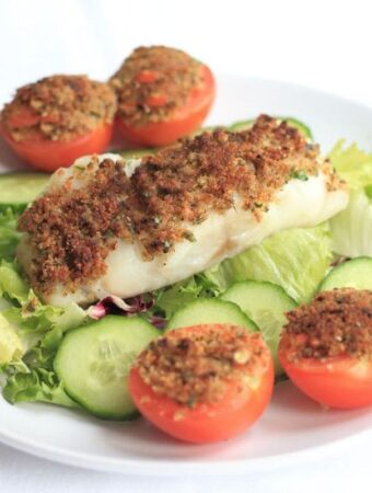 Grilled fish provencal served on top of a iceberg lettuce salad with sliced tomatoes.