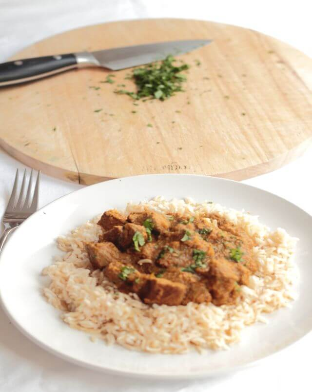 A plate of lamb chilli curry served on a bed of rice. A chopping board with a knife and chopped coriander in the background.