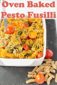 Oven baked pesto fusilli with a serving spoon in. Pin title text overlay at top.