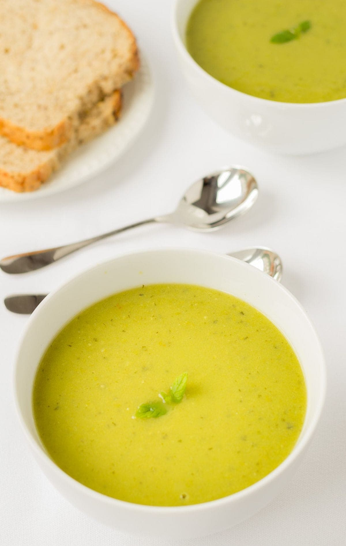 A bowl of pea and mint soup in the foreground with another bowl of soup in the background separated by soup spoons and a plate of sliced bread.