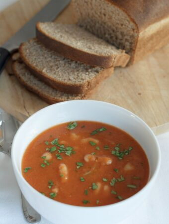 A bowl of tomato and white bean soup garnished with chopped basil. A sliced loaf of wholemeal bread in the background.