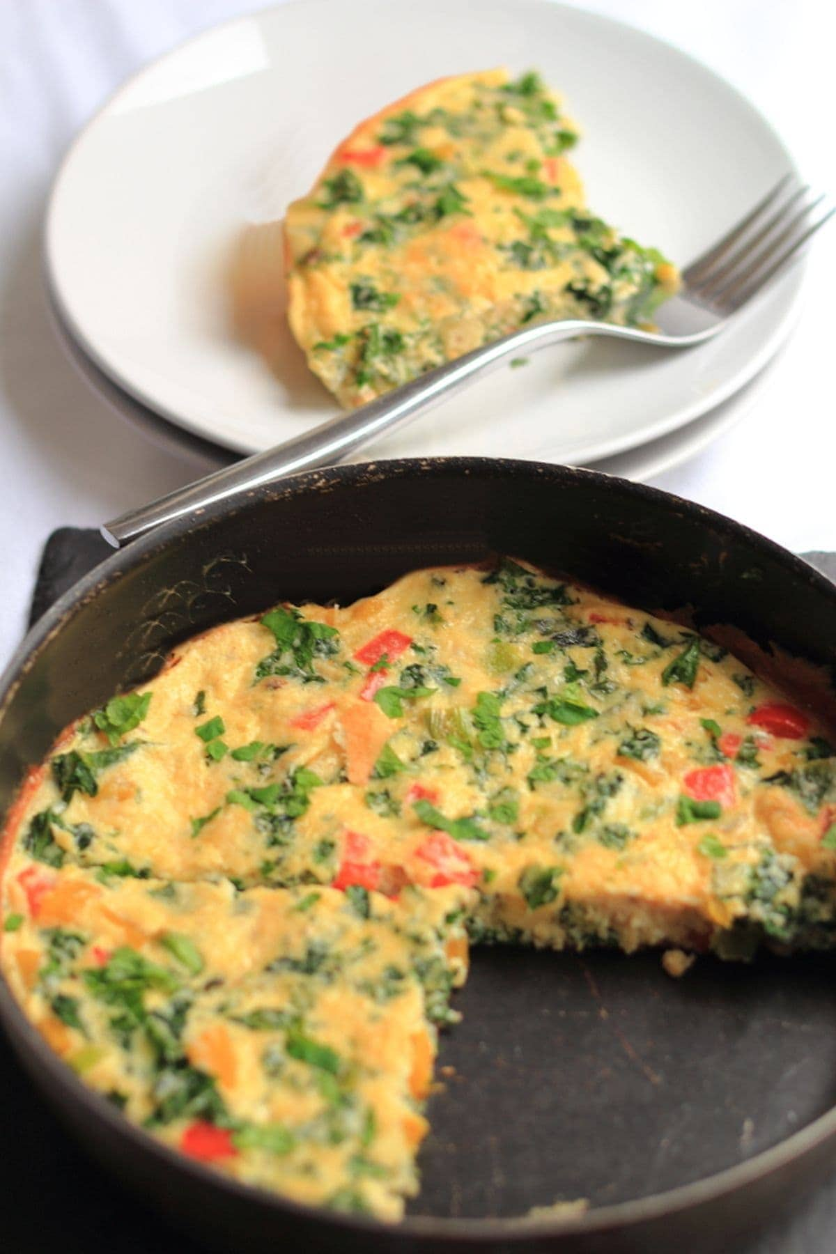 A poaching pan with the kale and pepper frittata in it. A slice taken out and placed on a small side plate with a fork in the background.