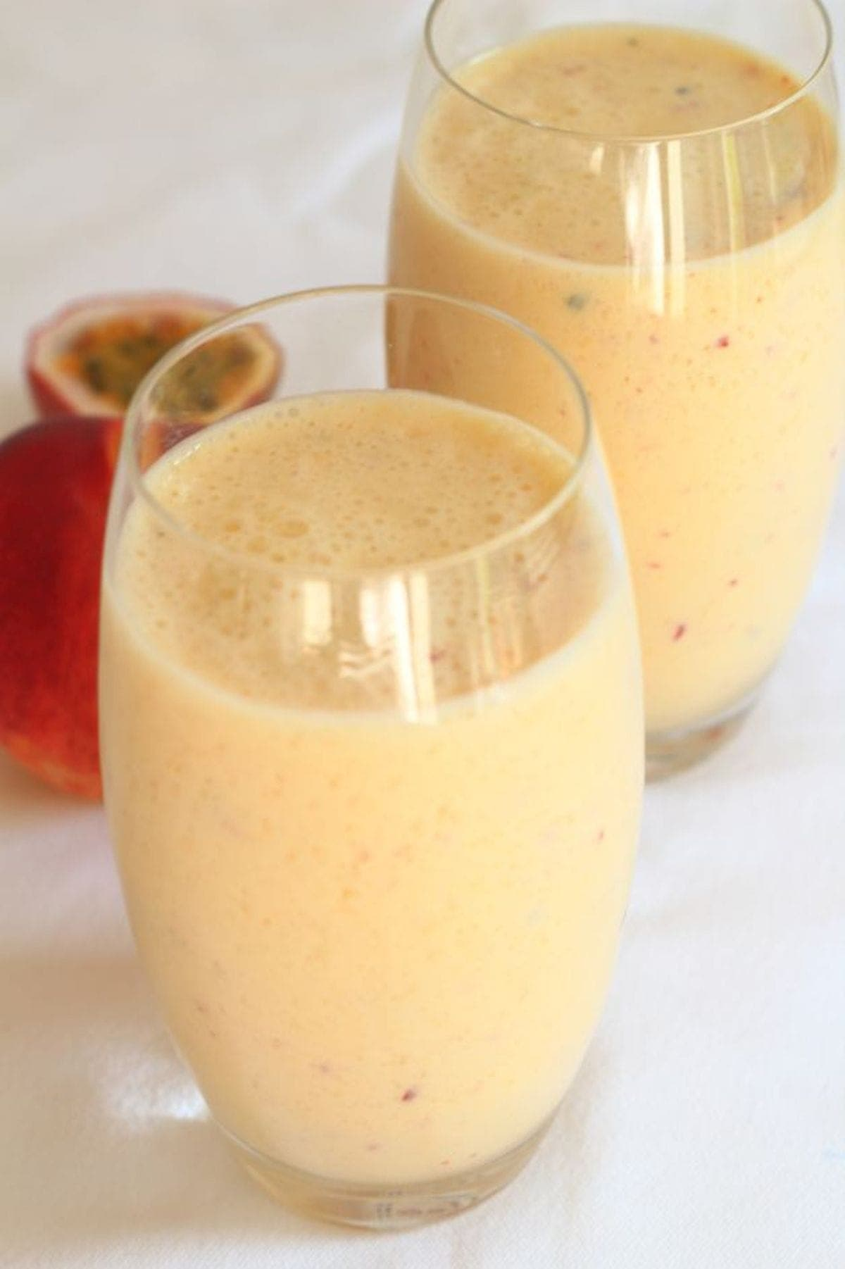 Two glasses of mango peach and passion fruit smoothie with a passion fruit in the background.