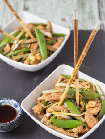 Two square bowls of turkey stir fry with sugar snap peas and chop sticks standing up in the bowls.