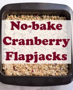Birds eye view of a square cake tin with cranberry flapjack in ready to cut up. Pin title text overlay in the middle.