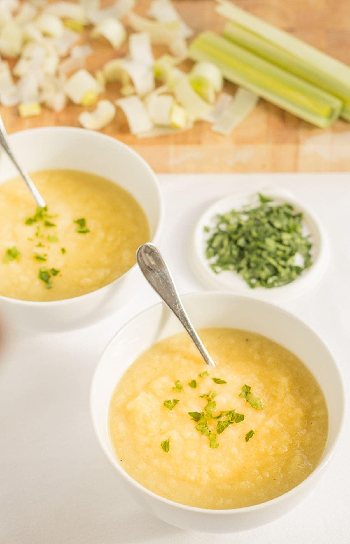 Two bowls of Scottish leek and potato soup diagonally across from each other with spoons in. Assortment of chopped vegetables around the top of the bowls.