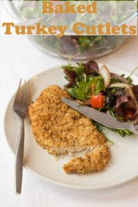 A baked parmesan turkey cutlet on a plate with a knife and fork and side salad. Pin title text overlay at top.