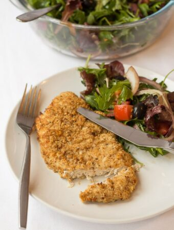 A baked parmesan turkey escalope on a plate with a knife and fork and side salad.