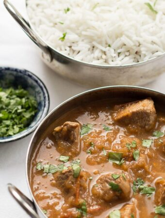 A balti dish of skinny lamb curry with a small dish of chopped coriander and a balti dish of rice in the background.