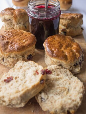 A chopping board with wholemeal cranberry scones on and a pot of jam with a spoon in the middle. A scone cut in half at the front.