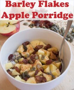 A bowl of barley flakes and apple porridge with a spoon in. A halved apple and assortment of nuts and seeds surrounding the bowl at the top. Pin title text overlay at top.