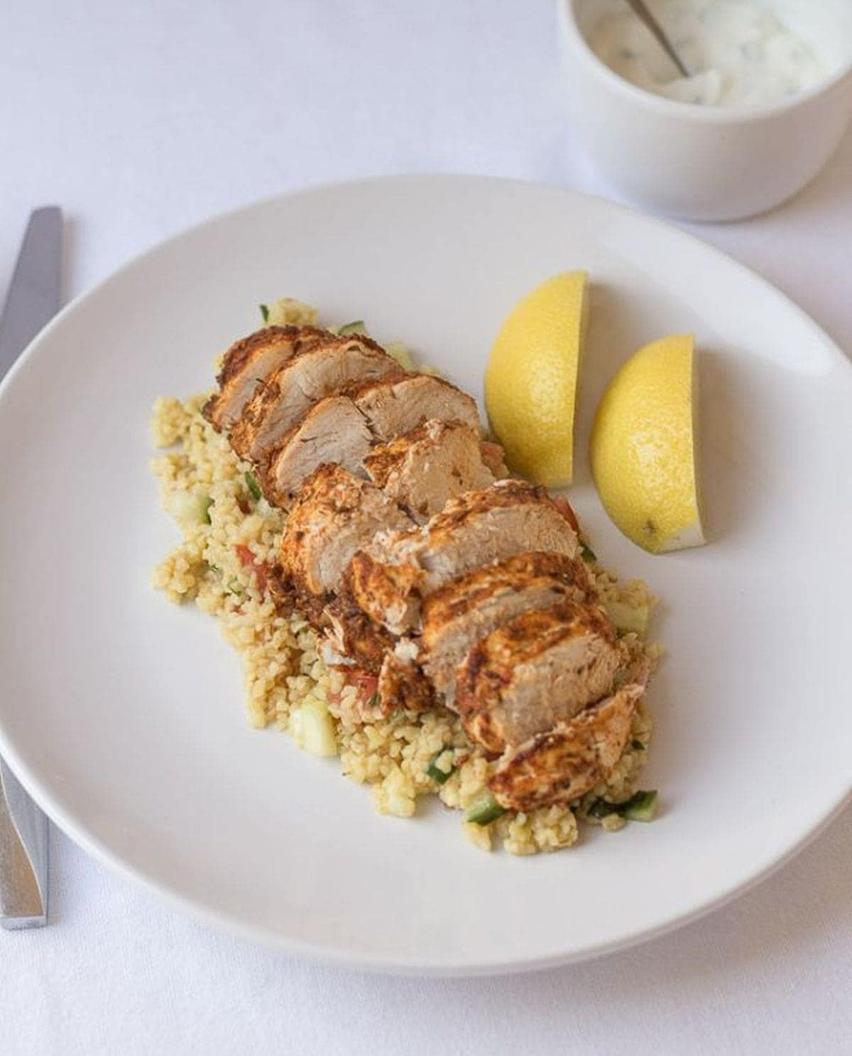 Sliced cajun spiced oven baked chicken on bulghur wheat with two lemon quarters on the side of the plate.