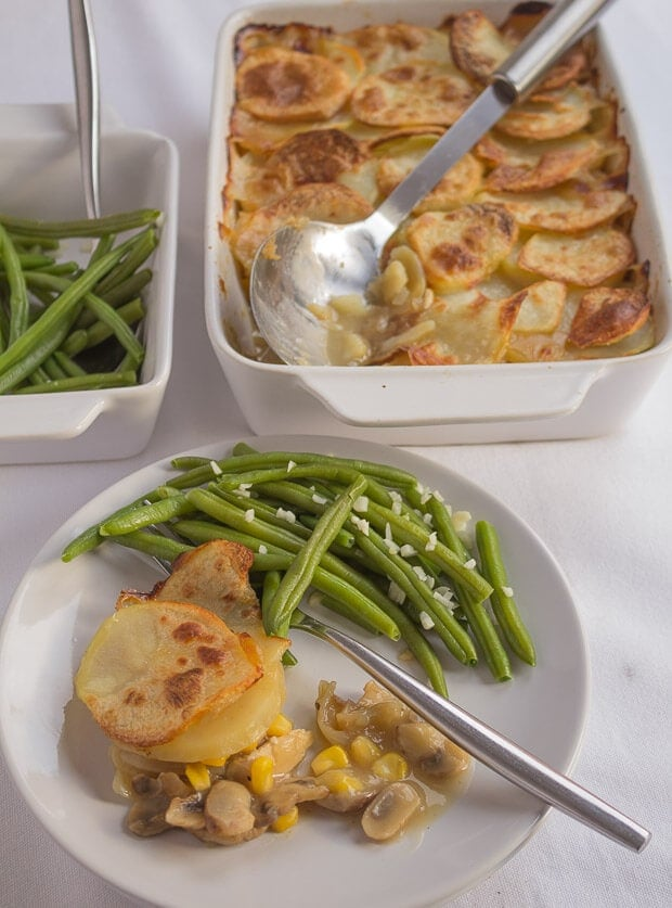 Served chicken sweetcorn and mushroom bake on a dinner plate with green beans and a fork. Serving dish of green beans and casserole dish in the background.