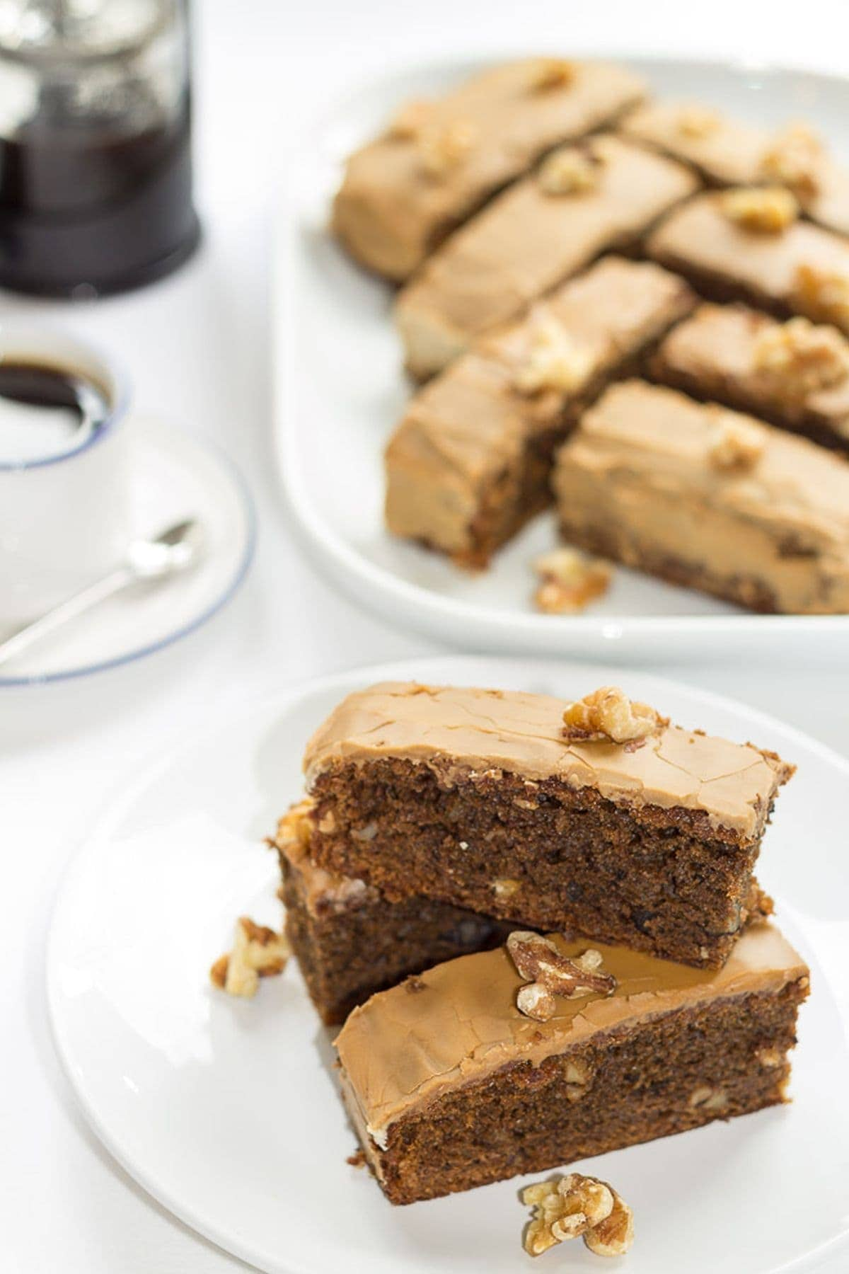 A round plate with slices of coffee walnut cake on at the front. A large serving plate with the remaining slices on in the background. A cup of coffee and cafetiere to the left hand side.