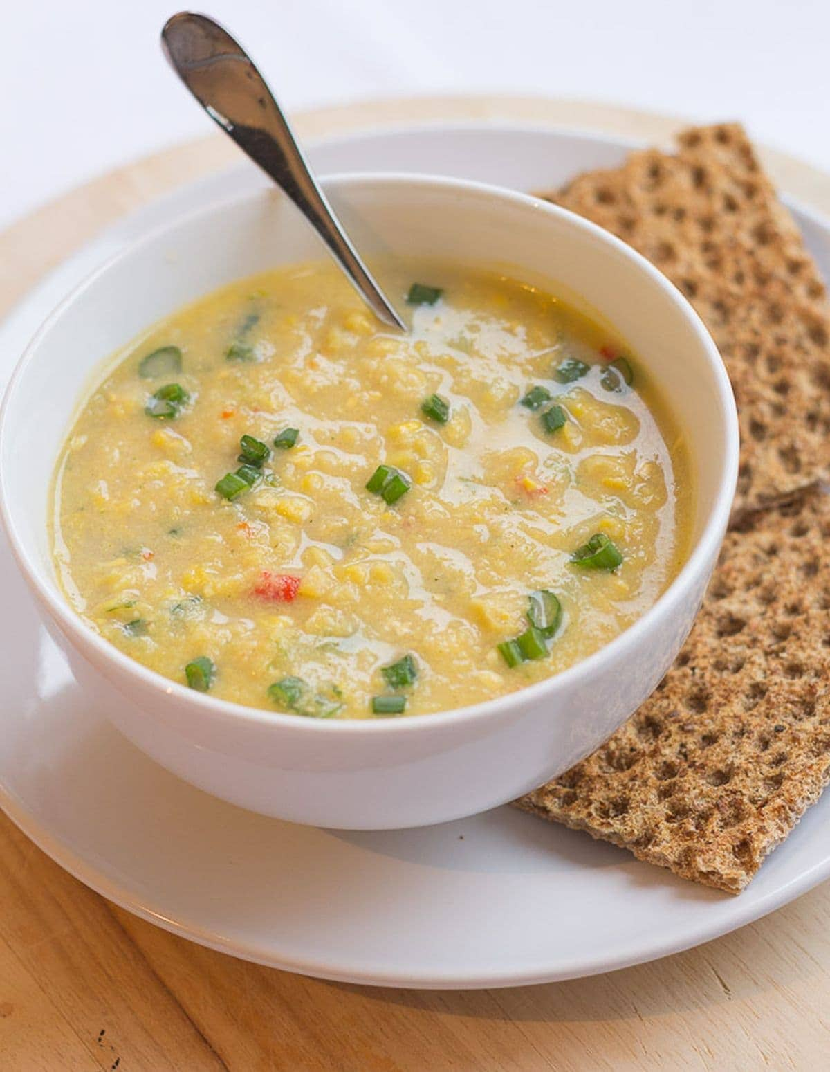 A bowl of creamy sweetcorn chowder with a spoon in. Crispy rye breads to the side.