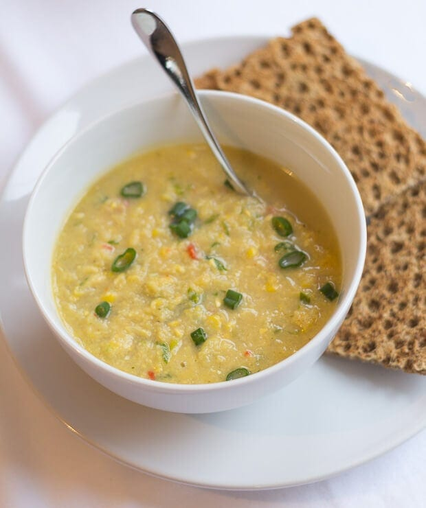 A bowl of creamy sweetcorn chowder on a plate with a spoon in and crisp breads behind the bowl.