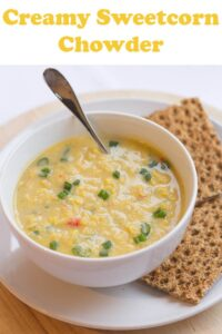 A bowl of creamy sweetcorn chowder with crispy rye breads to the side.