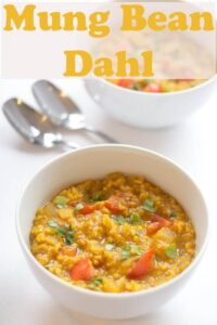 Two bowls of moong dall dahl with serving spoons in between.