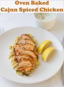 Oven baked cajun spiced chicken on a bed of bulgur wheat with lemon wedges to the side. Pin title text overlay at top.