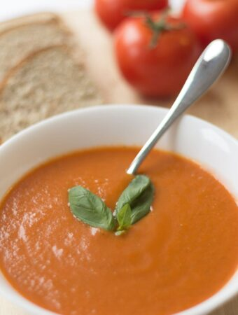 A bowl of simple skinny tomato soup garnished with a basil leaf and spoon in. Sliced wholemeal bread and 3 tomatoes in the background.