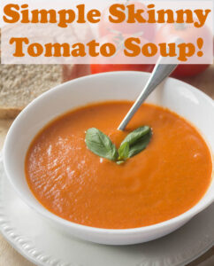 A bowl of skinny tomato soup garnished with 2 basil leaves and with a spoon in ready to eat.