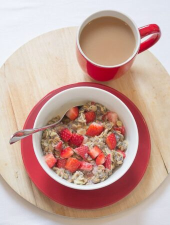 A bowl of strawberry and almond rye flakes porridge with chopped strawberries on top and a spoon in. A Cup of tea alongside the bowl.