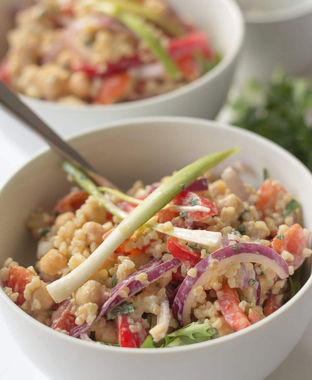 Two bowls of bulgur chickpea salad one in front of the other garnished with spring onions.