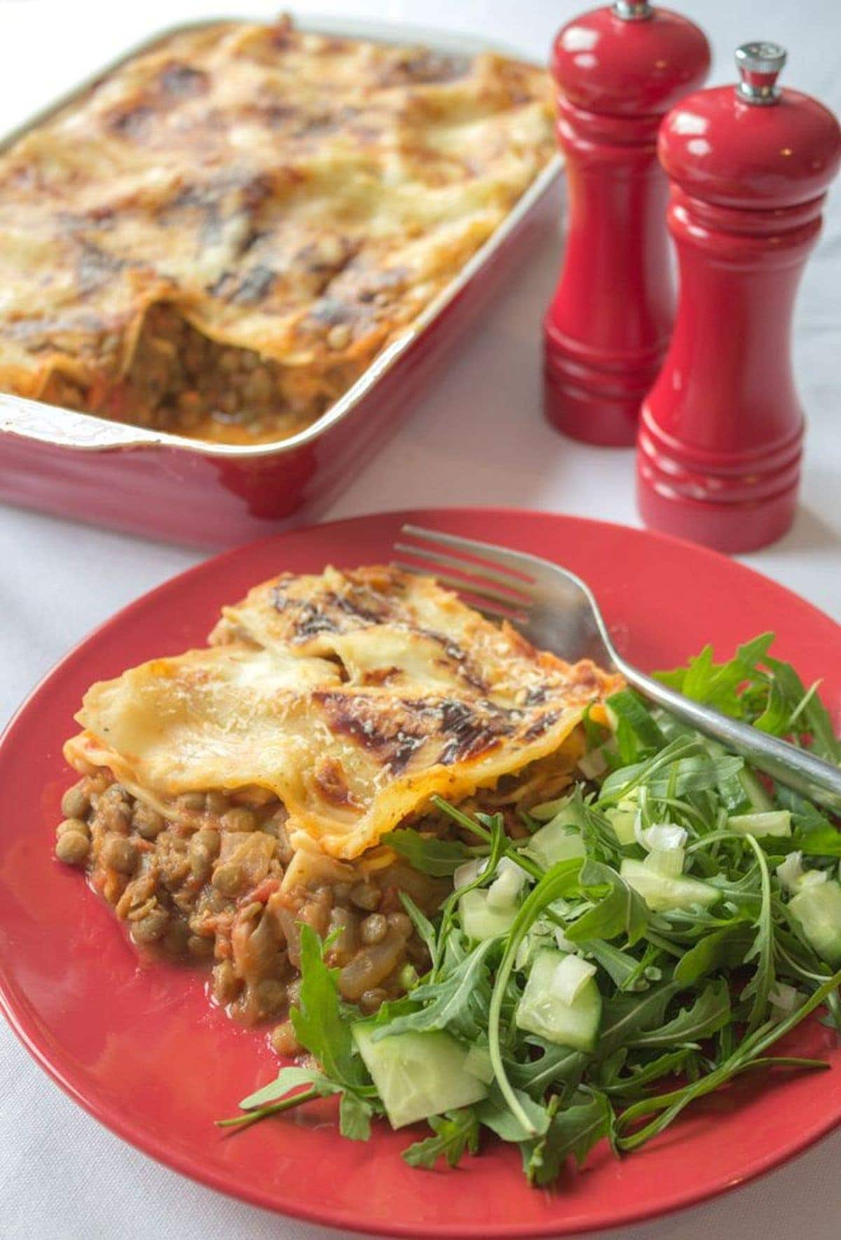 A portion of green lentil lasagne served with side salad on a plate. The rest of the lasagne dish and salt and pepper cellars in the background.
