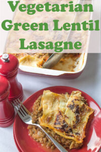 Green lentil lasagne served on a plate with serving dish behind it.
