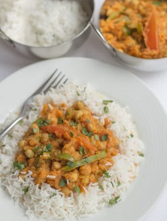 A plate of healthy chickpea curry garnished with chopped coriander. Two balti dishes of rice and more curry in the background.