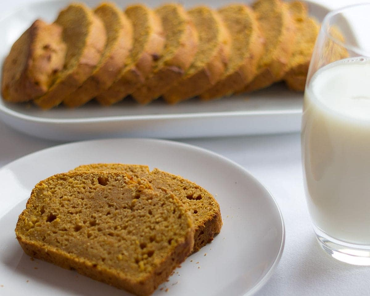 Two slices of pumpkin gingerbread on a plate with a glass of milk to the side. The rest of the loaf sliced and on a square plate in the background.