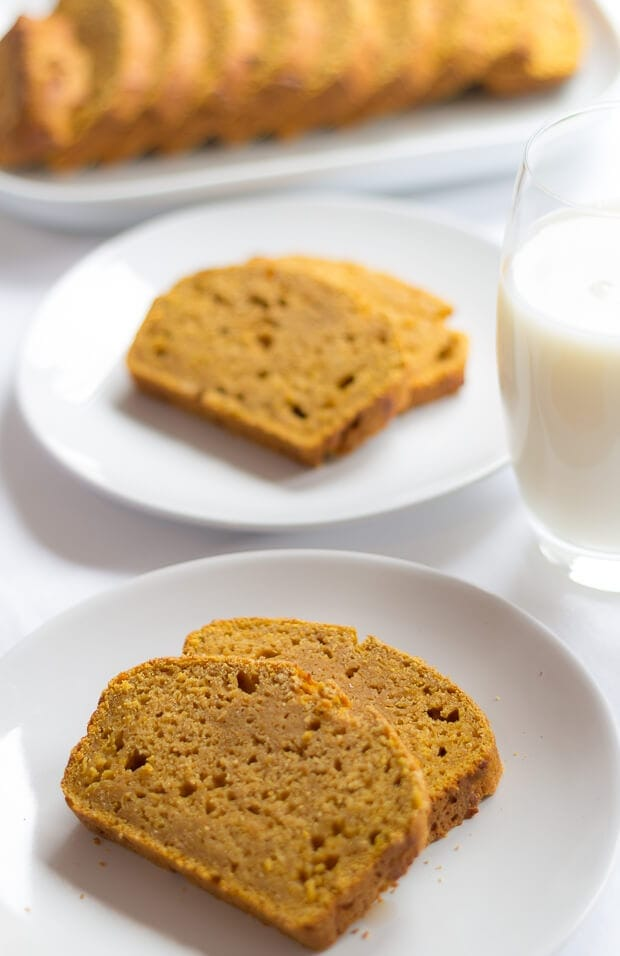 Two plates with two slices of pumpkin gingerbread on, one in front if the other with a glass of milk in between.
