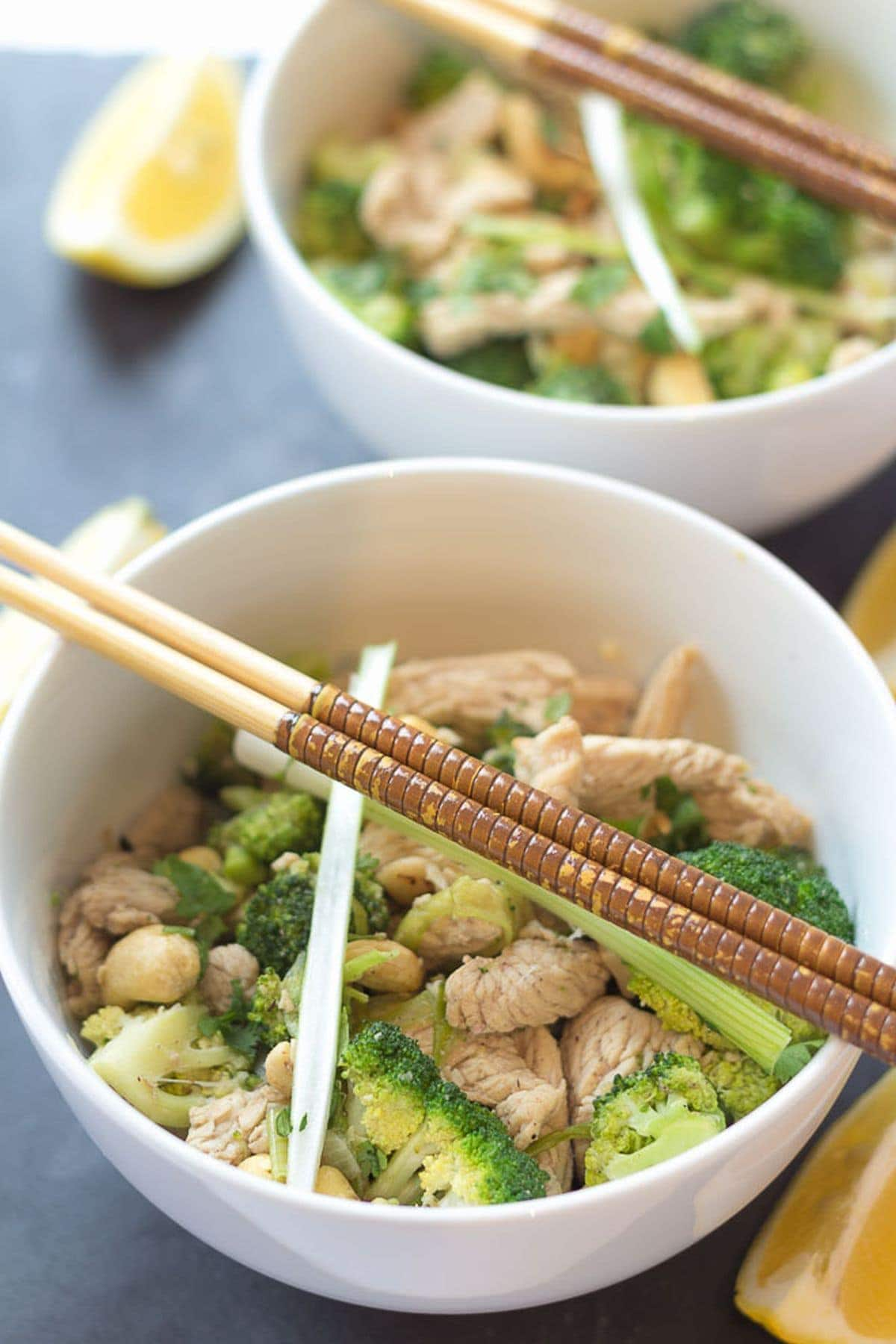 Two bowls of turkey and broccoli stir fry one in front of the other with chopsticks on. Lemon wedges to the side of the bowls.