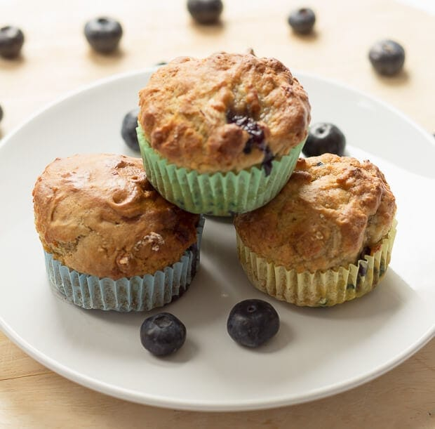 Three blueberry banana muffins stacked on a white plate with some blueberries scattered all around.