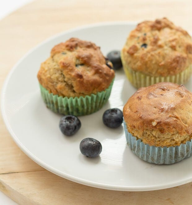A plate of 3 blueberry banana muffins with some blueberries scattered around the plate.