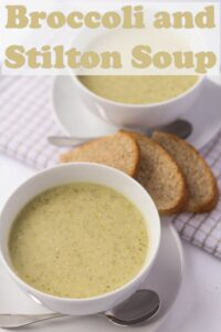 Birds eye view of a two delicious bowls of broccoli and stilton soup with slices of wholemeal bread in between.