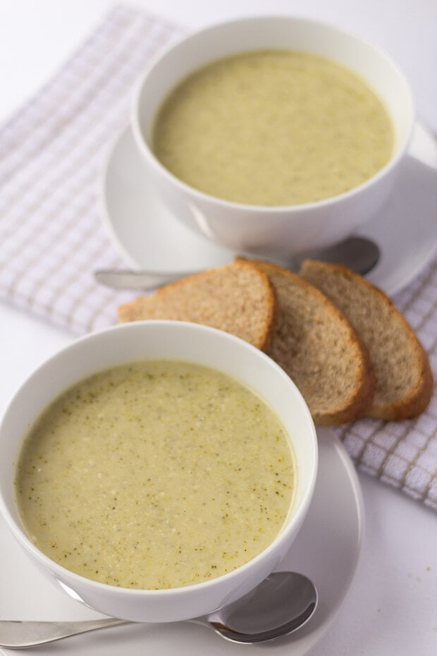 Close up birds eye view of two bowls of broccoli stilton soup with slices of bread in between.