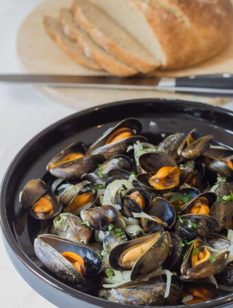 Cooked moules marinieres in a large bowl with a freshly made sliced cob loaf in the background.
