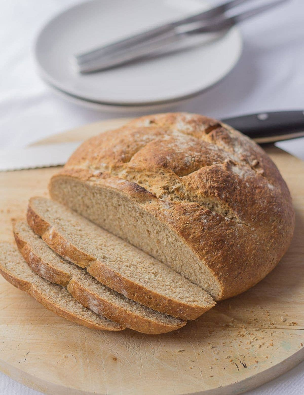 A wholmeal cob loaf on a round bread board with three slices cut off. Bread knife and side plates with knifes on in the background.