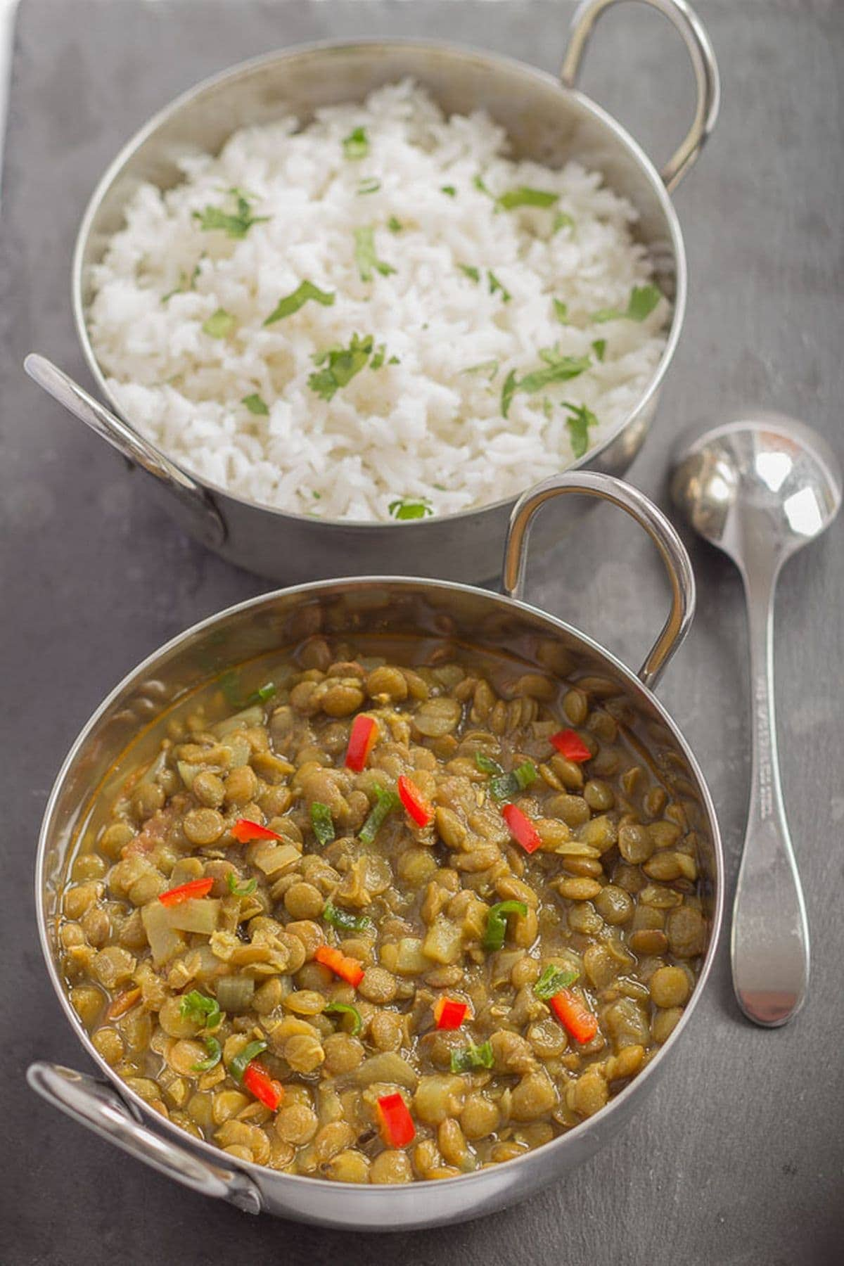 Two balti dishes one in front of the other. Front balti dish has green lentil dahl in it and the back one has bismati rice garnished with chopped coriander.