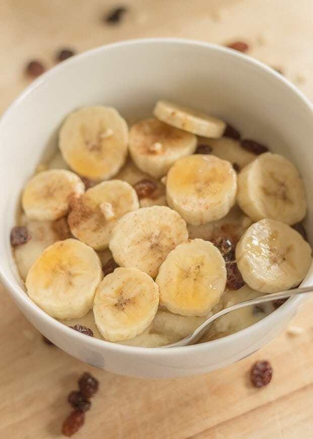 Close up of a bowl of semolina breakfast porridge decorated with sliced bananas.