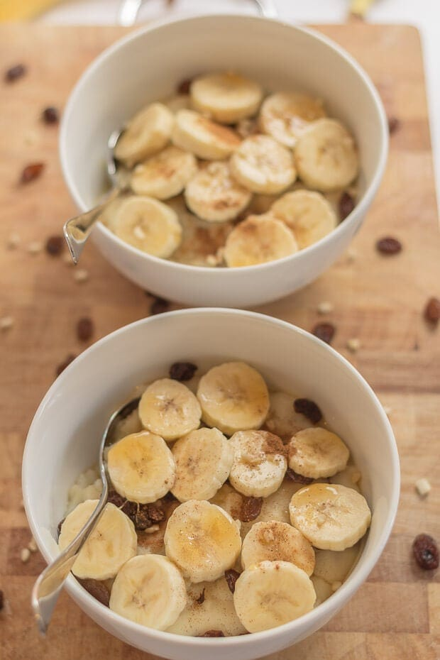 Birds eye view of two bowls of semolina breakfast porridge decorated with sliced bananas and serving spoons in each bowl.