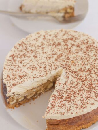 Tiramisu cheesecake with a slice taken out of and on a plate in the background.